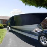 Starboard and bow of blue hulled boat sitting on a trailer in a driveway