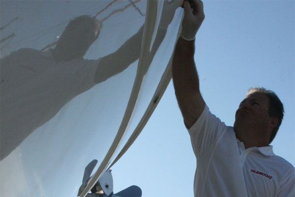 Man wearing white glove holding a sponge applying Glidecoat ceramic coating to the hull of a 1998 52' Princess