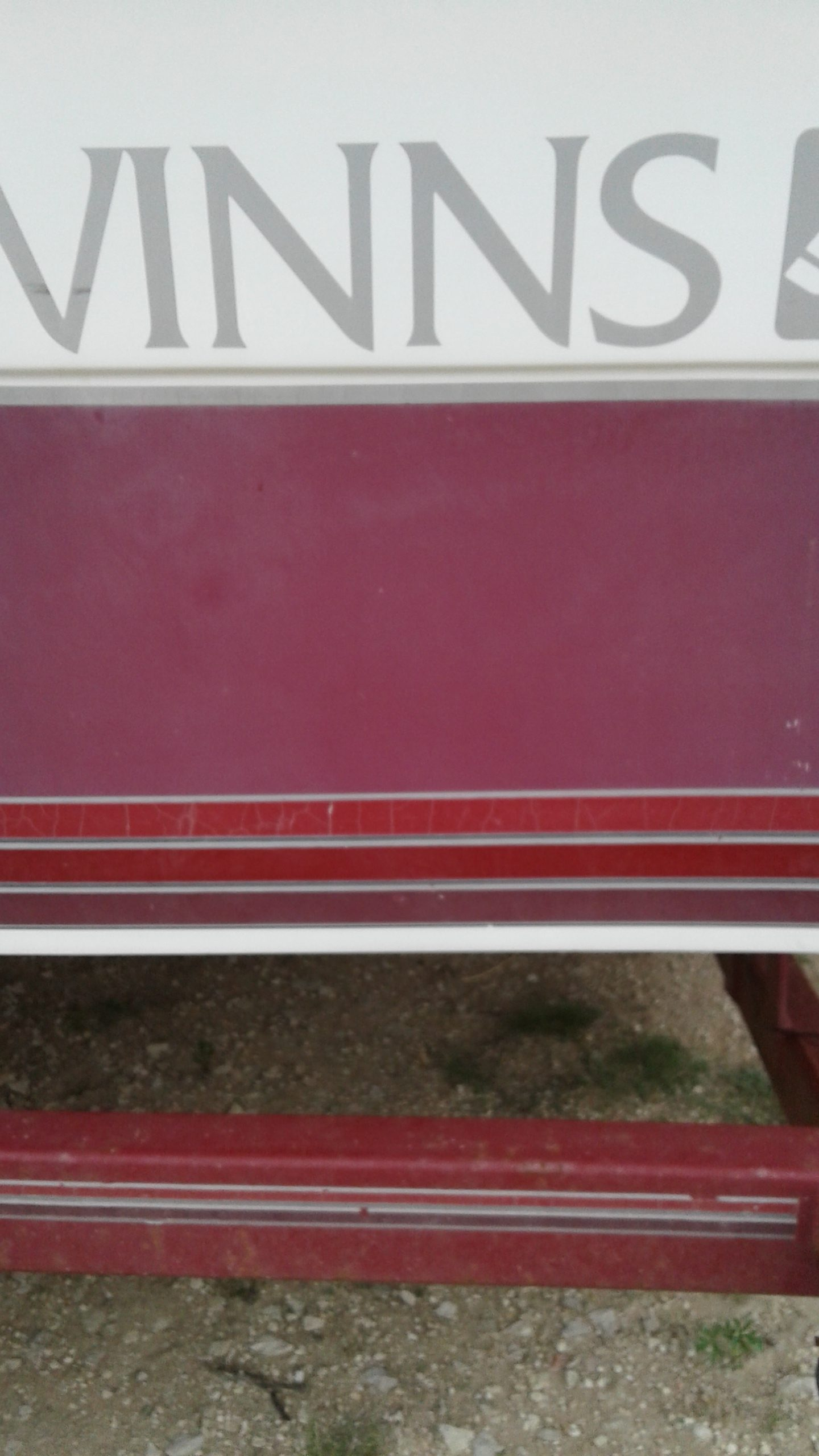Faded and oxidized red and white hull color on boat