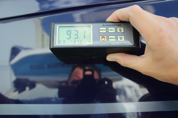 Man taking photo holding gloss meter reading with 93.1 displaying on the screen