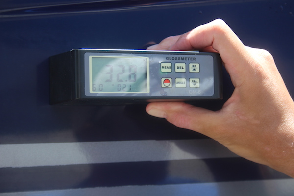 Man holding gloss meter with 32.8 reading on blue hull of Sea Ray Sundancer