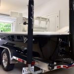 The reflection of the black hulled Yellowfin boat sitting in a garage